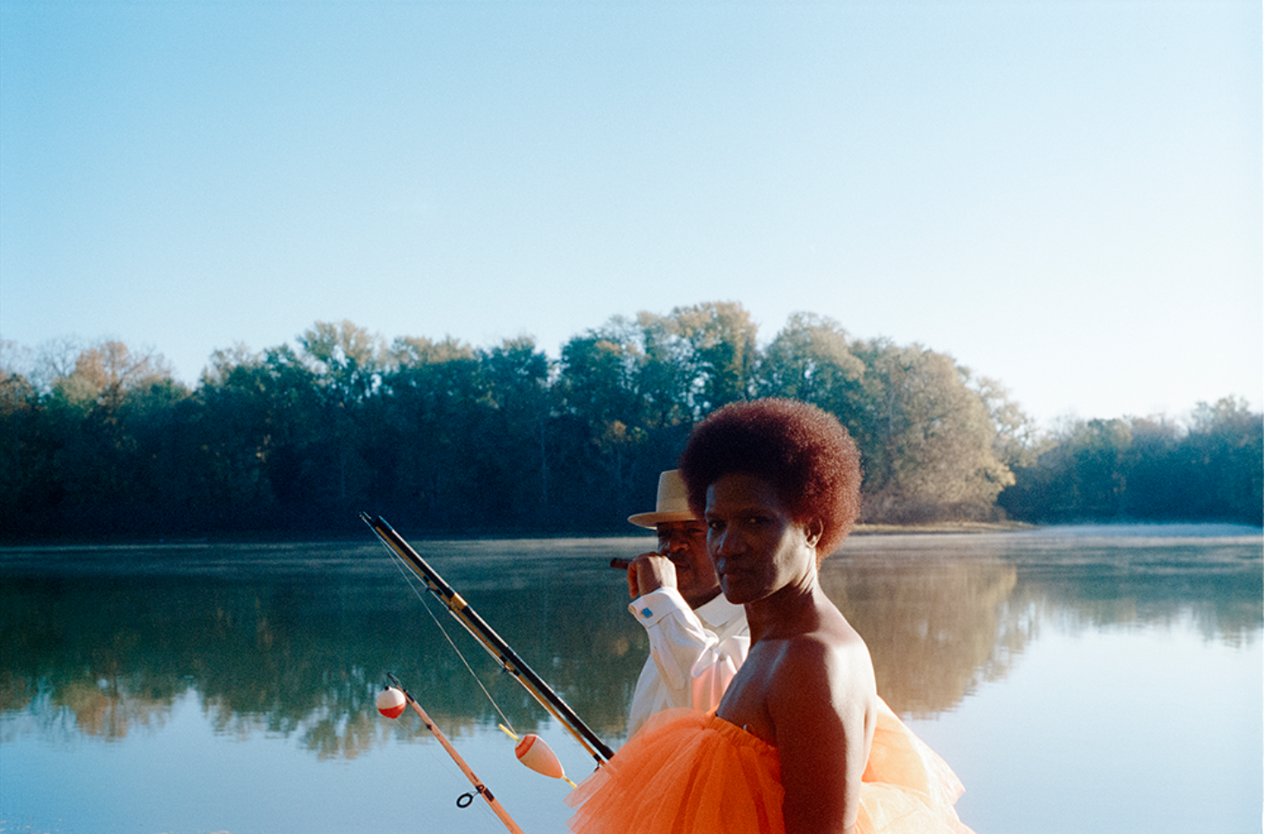 A Black woman in an orange dress and a Black man in a white suit and hat hold fishing rods with a lake in the background.