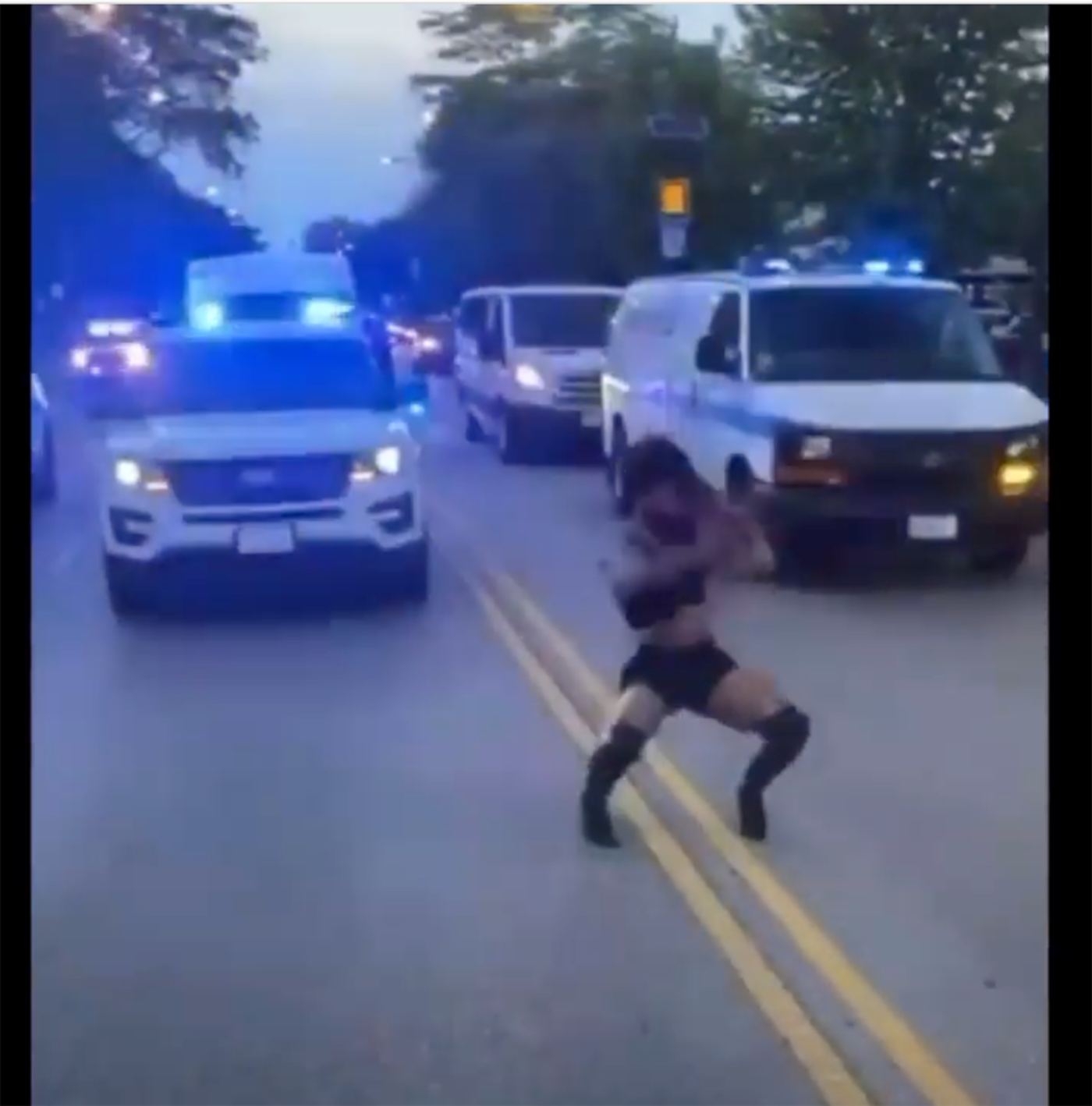 A Black woman in long black boots, shorts, and a tank top dances in the middle of the road in front of several police vehicles with their lights on.